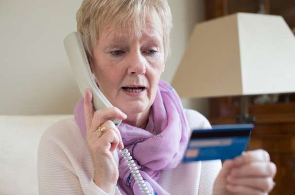 Elder Fraud Image of Woman Reading Credit Card Over the Phone