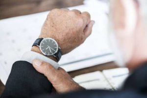 Succession planning image of business owner looking at watch