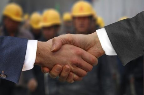 Third Party Sales Businessmen shaking hands in front of employees in hardhats.