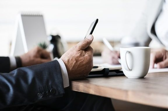 planning for your business future with businessman sitting at desk and holding a mobile phone