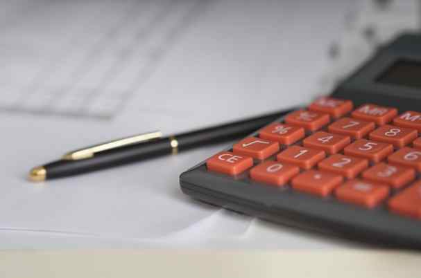 Life insurance underwriting process image shows documents, calculator and pen
