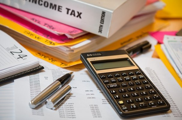 IRS withholding tool photo shows tax documents and calculator