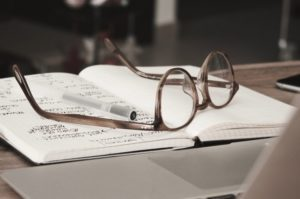 Glasses on a journal indicating doing research.