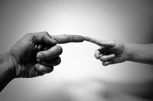 Charitable giving what to do before you donate depicts a man and child touching fingers