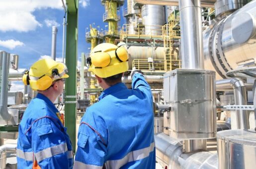 Financial planning for oil and gas industry professionals depicts two men in protective helmets and coveralls in front of equipment.
