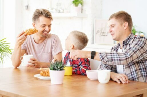 Financial planning and investment management for LGBTQ shows two men and their young son eating breakfast at the table.